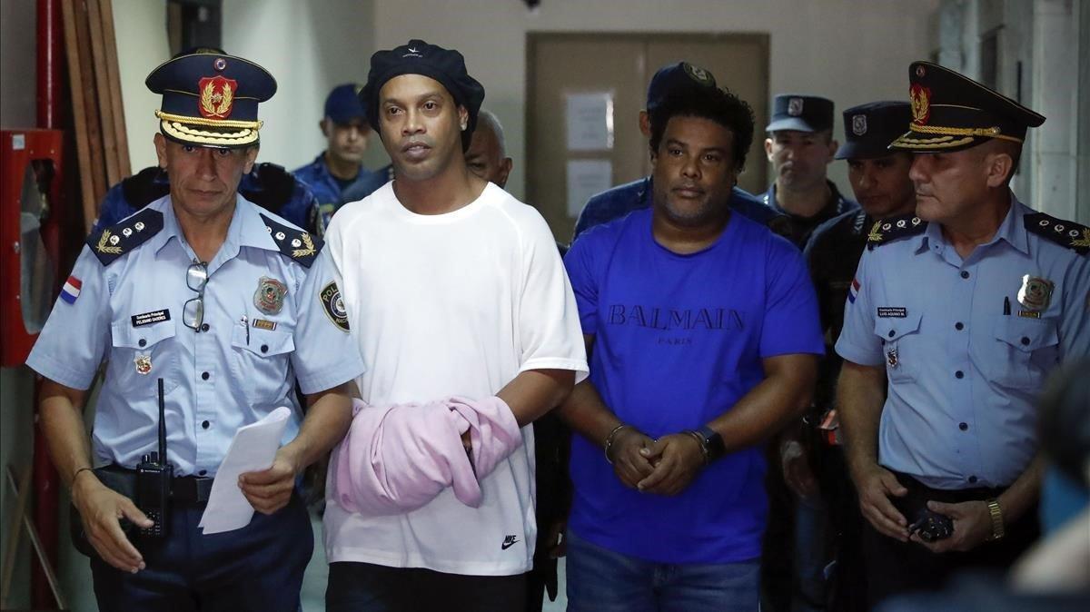 Ronaldinho y su hermano Roberto, esposados y conducidos por la policía a declarar en los juzgados de Asunción.