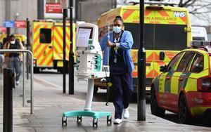 Una trabajadora del Servicio Nacional de Salud traslada una máquina de diálisis en el Royal London Hospital.