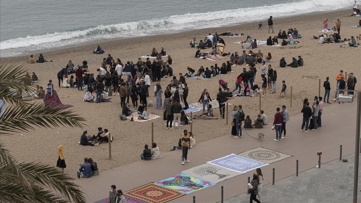 Playa de la Barceloneta por la tarde, donde numerosos jóvenes quedan para tomar algo sobre la arena.