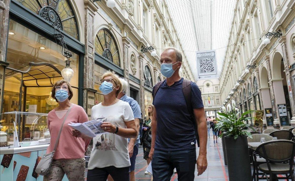 Paseantes con mascarilla por el centro de Bruselas.