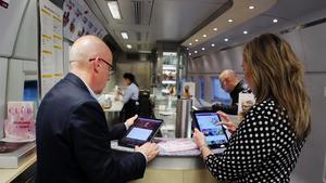 Pasajeros del AVE Barcelona-Madrid utuilizan la nueva aplicación wifi en el tren.