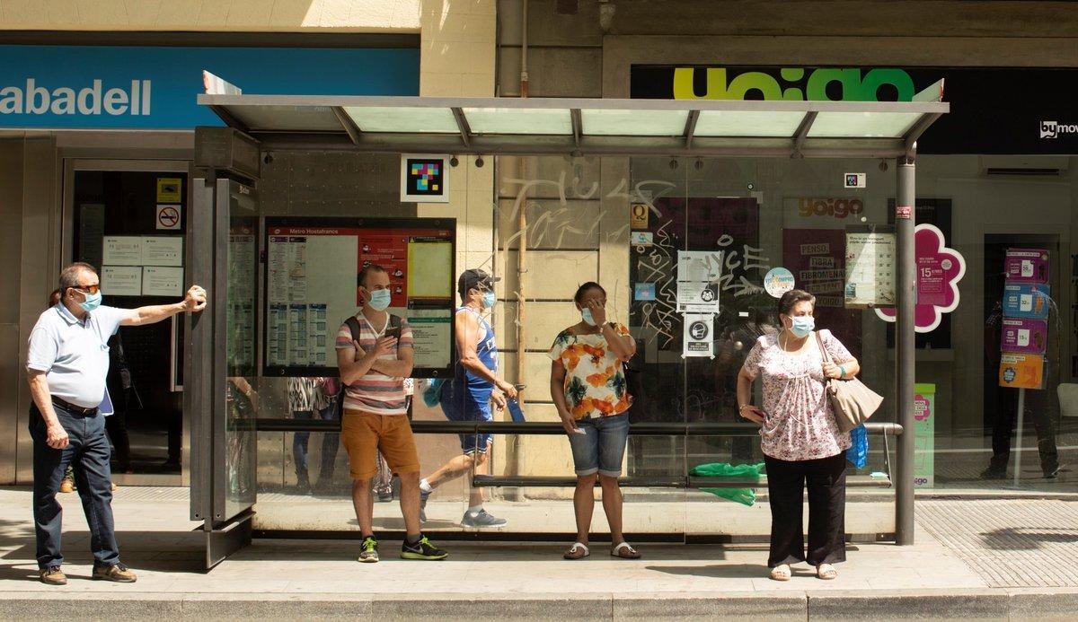 Varias personas esperan el autobús en una parada en Barcelona.