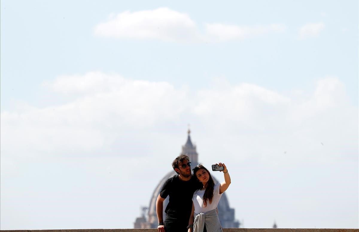 Una pareja en la terraza del Giardino degli Aranci (Jardín de los Naranjos) con la cúpula de San Pedro al fondo.