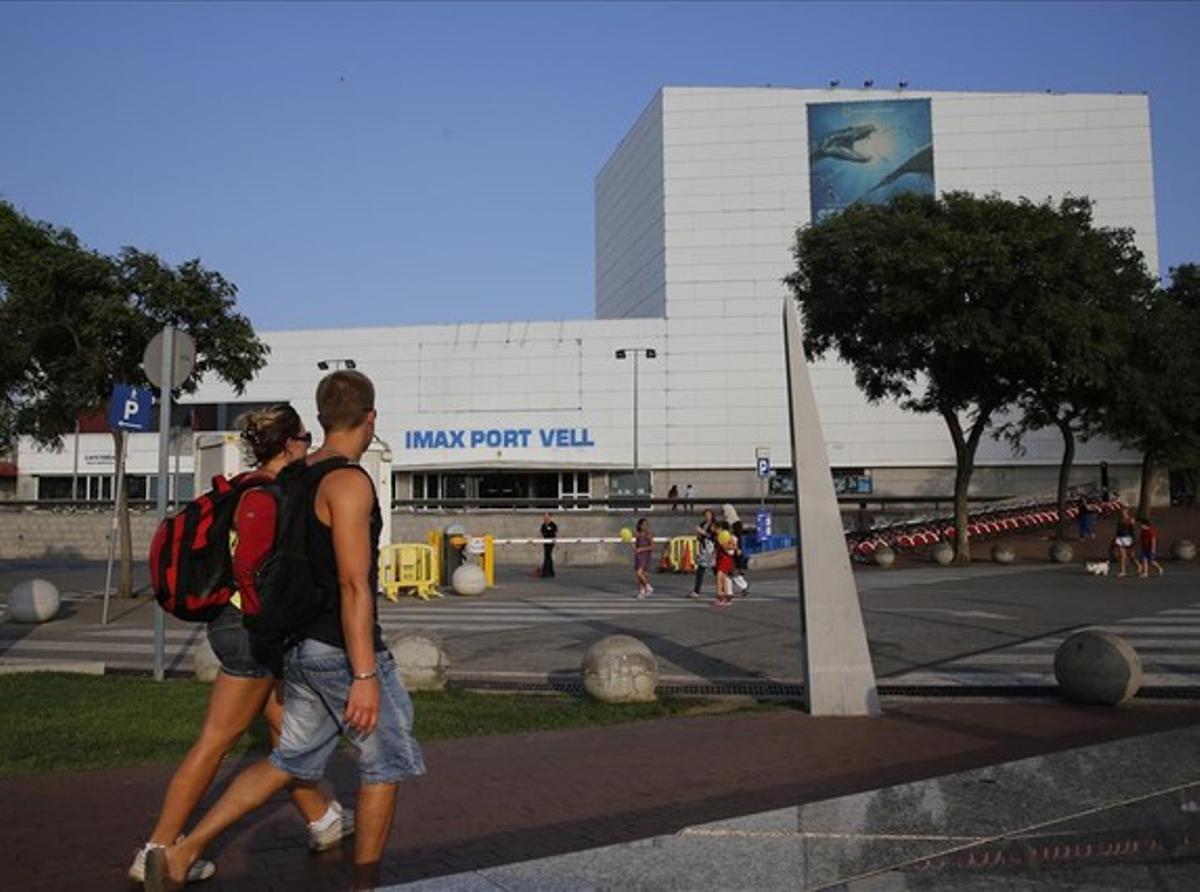 Unos turistas, la tarde del miércoles, pasean delante de la fachada del cine Imax Port Vell.