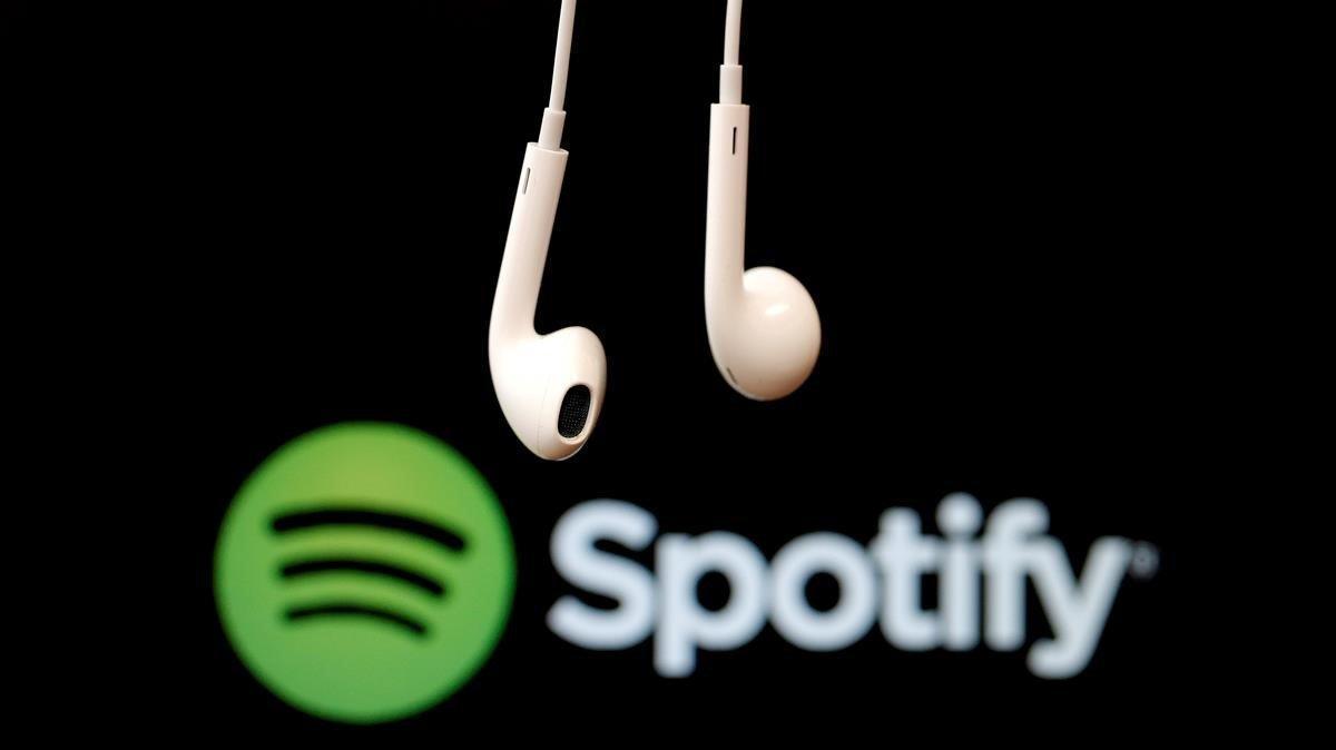 Unos auriculares ante un logo de Spotify