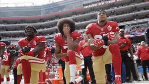 Colin Kaepernick, rodilla en tierra, en el centro de la imagen, escucha el himno de EEUU