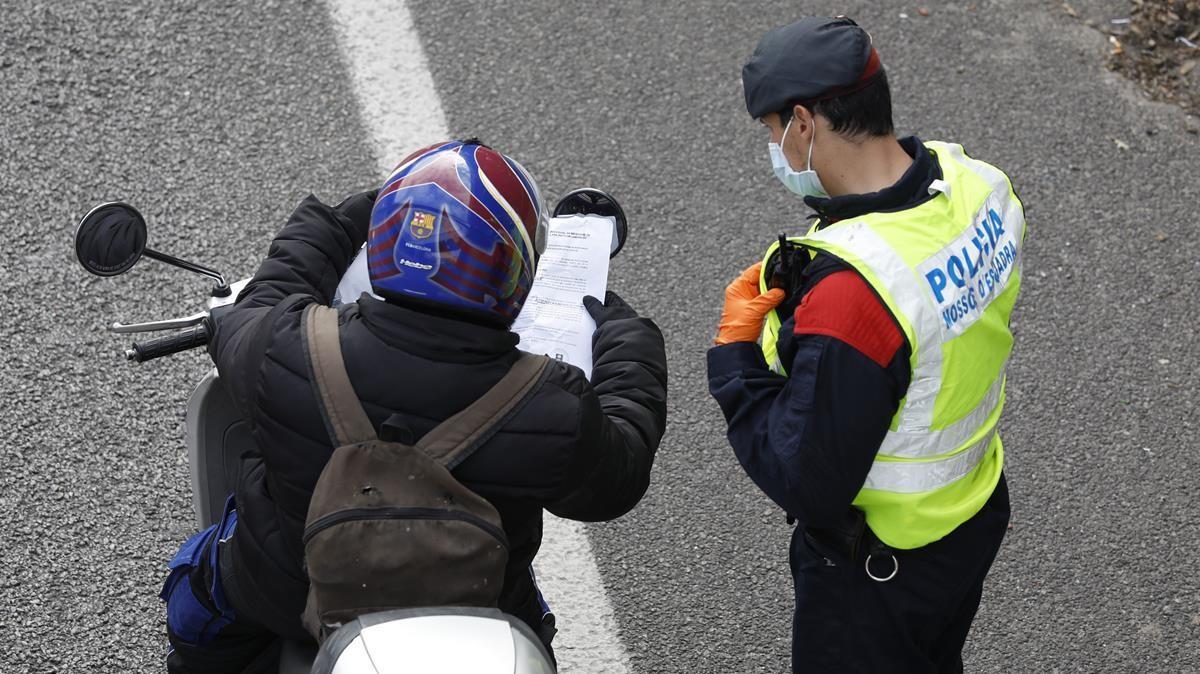 Un motorista muestra a un agente un justificante en un control de los Mossos en la Gran Via de Barcelona, junto a la Ciutat de la Justícia, el 7 de abril del año pasado.
