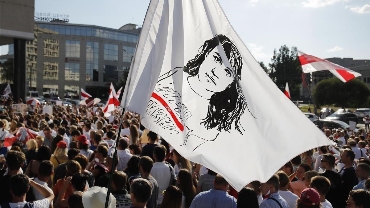 Manifestantes portan una bandera con un retrato de la líder opositora bielorrusa Svetlana Tikhonóvskaya, en Minsk.