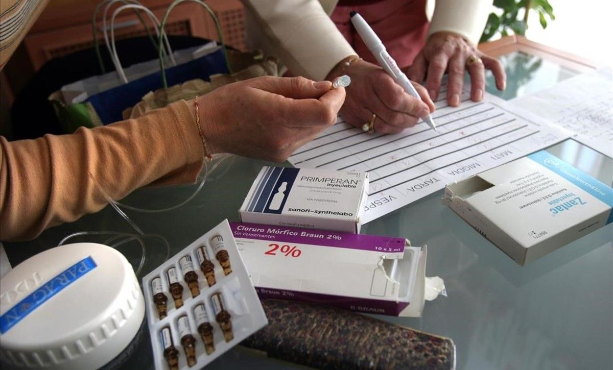 Dos enfermeras preparando los medicamentos para muerte digna en casa de un paciente.