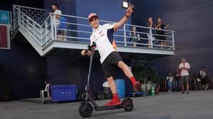 Marc Márquez sale, alegremente, de la sala de prensa del circuito de Buriram (Tailandia), montado en su patinete.