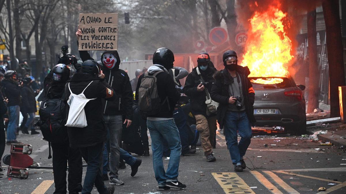 Un manifestantes muestra un cartel contra la violencia policial en una calle donde se ha prendido fuego a un vehículo aparcado.