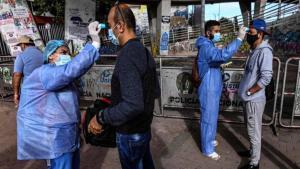 Personal médico en Colombia revisa la temperatura de transeúntes.