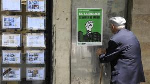 Un hombre observa un cartel de la manifestación contra los precios de los alquileres.