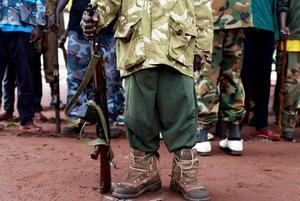 Un antiguo niño soldado sostiene una arma en una cerimonia de liberación de niños soldado en Yambio, Sudán del Sur