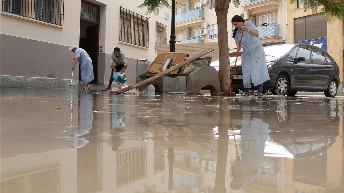 Vecinos de Orihuela limpian sus casas tras la tromba de agua.
