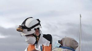 Un menor llegado en patera a las costas de Gran Canaria en brazos de un hombre protegido con un EPI.