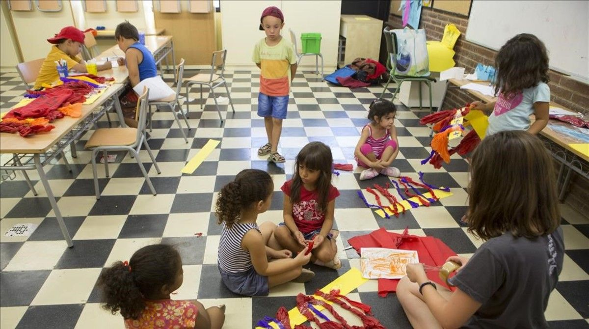 Un grupo de niños trabaja en la confección de unos disfraces, con la ayuda de una monitora.