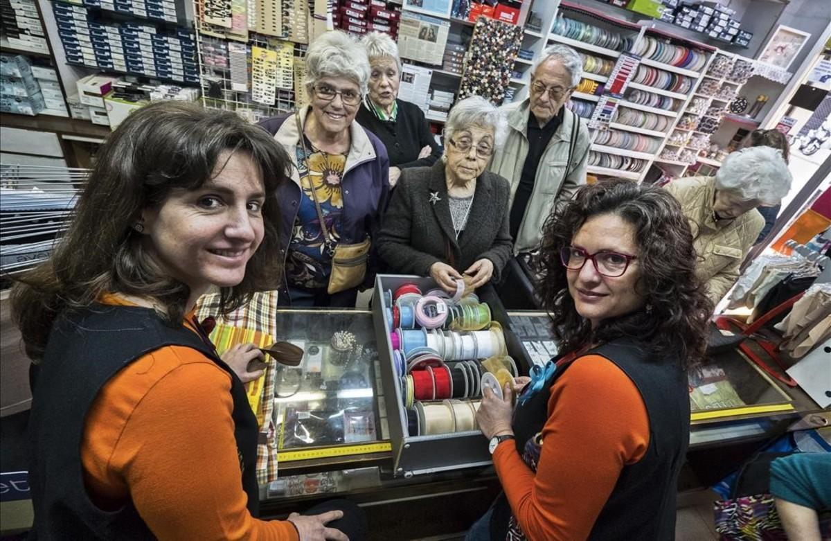 Las hermanas Glòria (izquierda) y Raquel Rivero, al frente de la mercería Esmar, con buena parte de la clientela mayor.