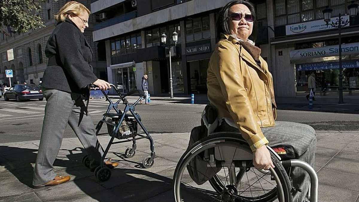 Paloma (en silla de ruedas) y Ana en una imagen de 2016 al lado del edifico donde ocurrió la tragedia.