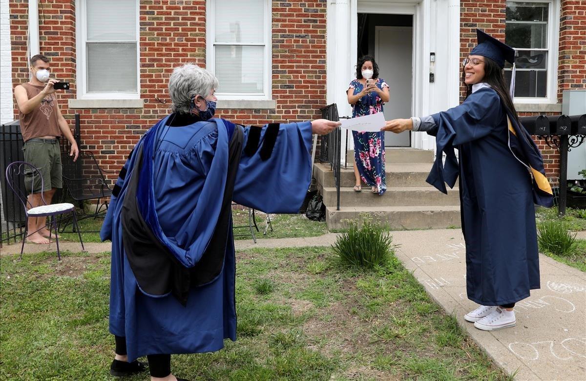 La graduada de la Universidad George Washington, Catalina Pérez, recibe una copia en papel de su diploma mientras mantiene La distancia social en una fiesta sorpresa de graduación.