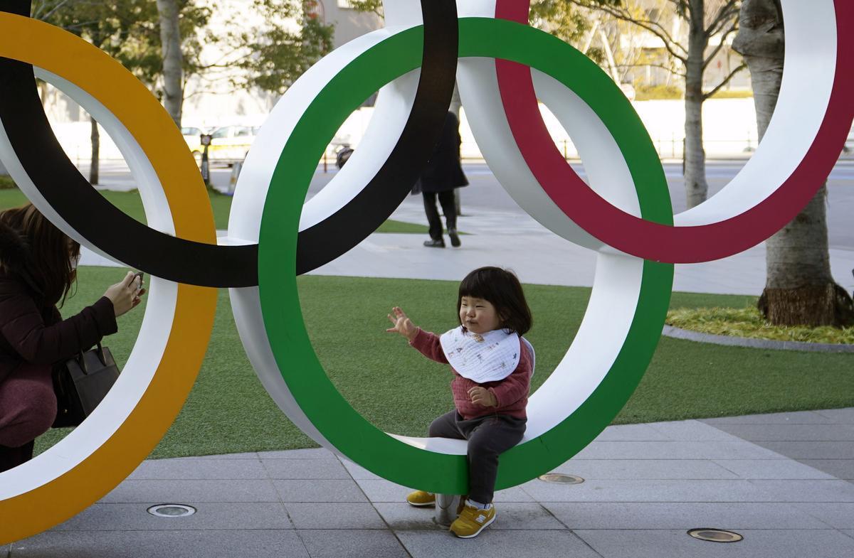 Una niña se deja fotografiar en los aros instalados a las afueras del Estadio Nacional de Tokio, este viernes.