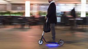 Un hombre conduce un patinete eléctrico.
