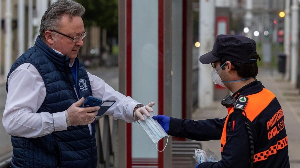 Un voluntario de Proteccion Civil repartiendo mascarillas a los viajeros de los autobuses urbanos de Sevilla