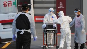 Médicos llevan a un infectado del covid-19 al hospital en Seúl, Corea de Sur