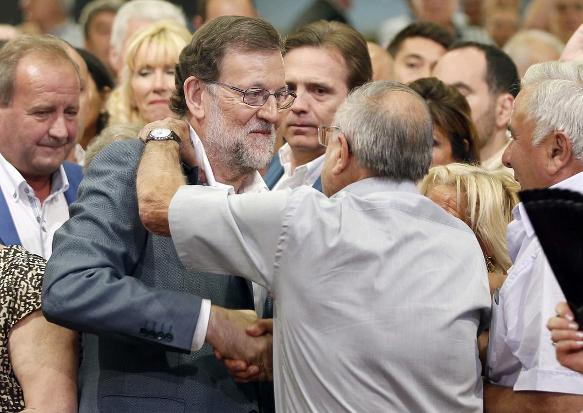 Rajoy saluda a un simpatizante a su llegada al mitin electoral que ha ofrecido en la Llotja de Lleida.