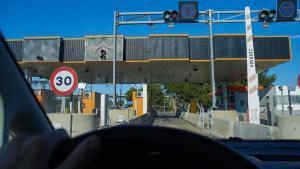 Conductor pasando a través de una antigua estación de peaje de la AP-7.