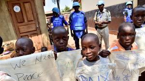 Niños esperan la llegada del Papa Francisco en un campo de refugiados en Bangui controlados por soldados de Naciones Unidas.