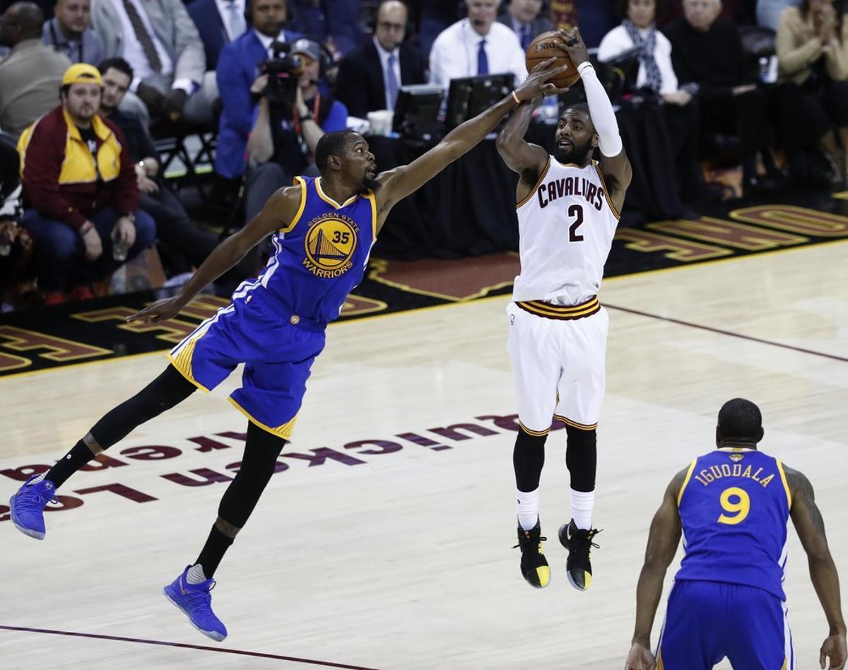 JGM157 CLEVELAND (ESTADOS UNIDOS) 08/06/2017.- El jugador de los Cavaliers Kyrie Irving (c) lucha por el balón con Kevin Durant (i) de los Warriors durante el tercer partido de las Finales de la NBA que enfrentó a los Warriors de Golden State contra los Cavaliers de Cleveland en el Quicken Loans Arena en Cleveland, Ohio (Estados Unidos) ayer, 7 de junio de 2017. EFE/Larry W. Smith