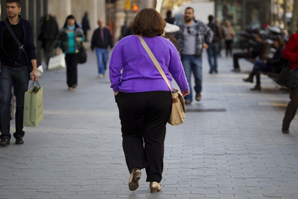 Una mujer con sobrepeso pasea por Barcelona.