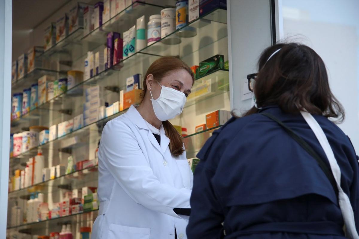 Una clienta conversa con una empleada a las puertas de una farmacia del centro de Madrid durante el confinamiento.