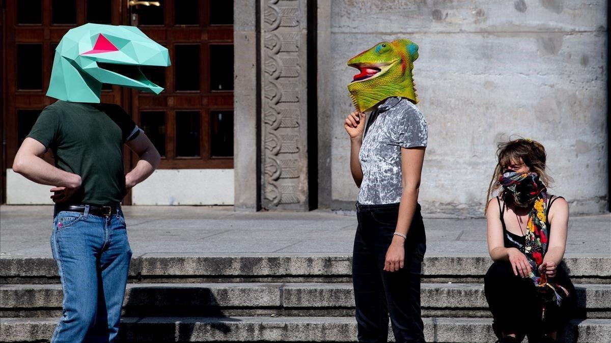 Manifestantes con mácaras de reptiles durante una protesta contra las restricciones y medidas implementadas para detener la propagación del coronavirus