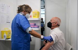 Una enfermera habla con un hombre justo después de que reciba la vacuna contra el covid-19.