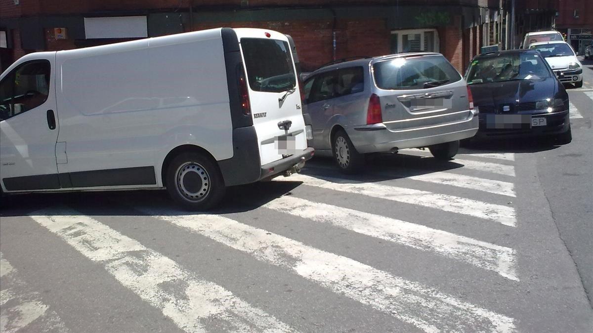 Vehículos aparcados en un paso de cebra del barrio de Horta de Barcelona.