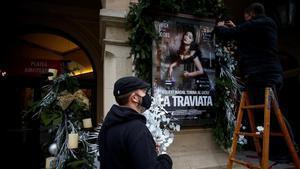 Dos trabajadores decoran el cartel de 'La Traviata' en la entrada principal del Gran Teatre del Liceu esta semana.