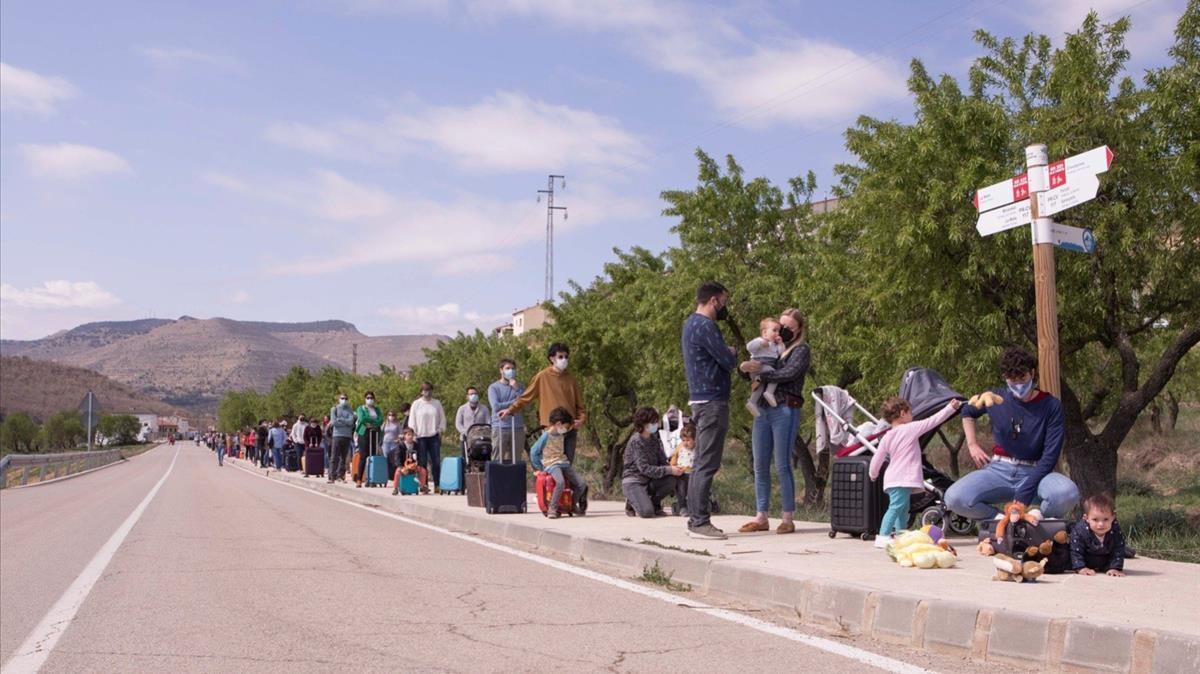 Los vecinos de La Mata (Els Ports, Castellón), en fila durante su protesta en la carretera del pueblo con un línea MAT.