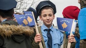 Un niño vestido de policía sostiene la bandera kosovar. este viernes, para celebrar los 10 años de independencia.
