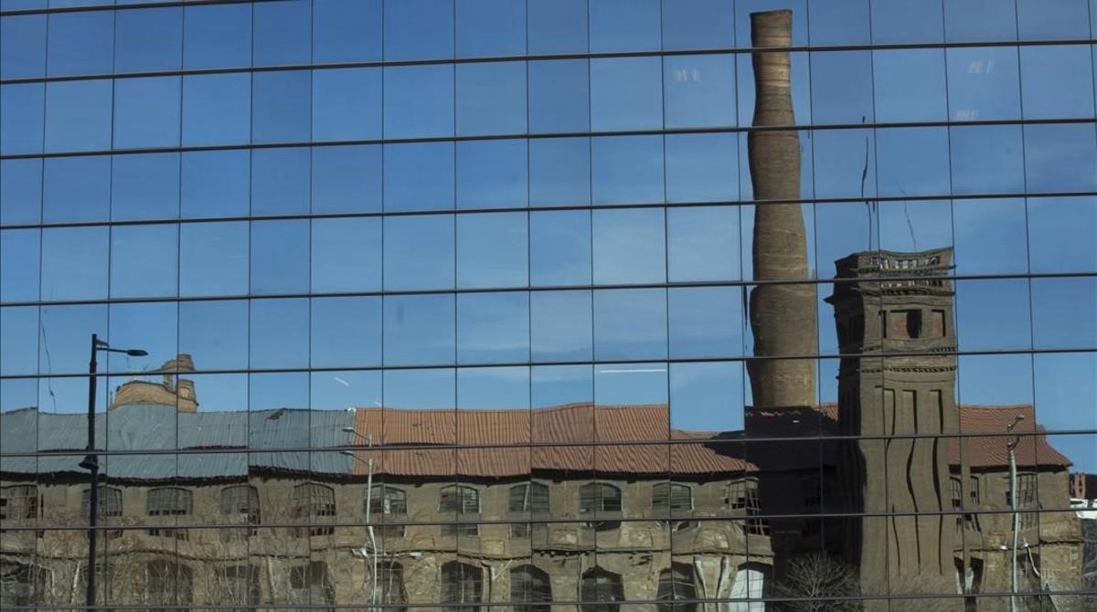 Reflejo del bloque siete de Can Batlló, que pronto se convertirá en nueva seve del EMAV, en la fachada de La Campana.