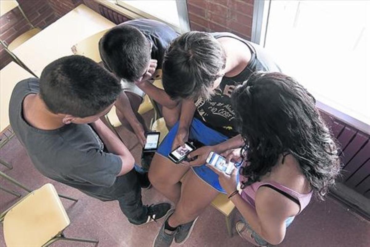 Cuatro alumnos de un grupo de mediación navegan por las redes sociales con sus móviles, en el instituto Torre Vicens de Lleida.