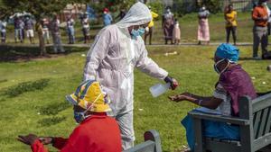Un sanitario rociando con un esprai las manos de una persona en Diepsloot, al norte de Johanesburgo.