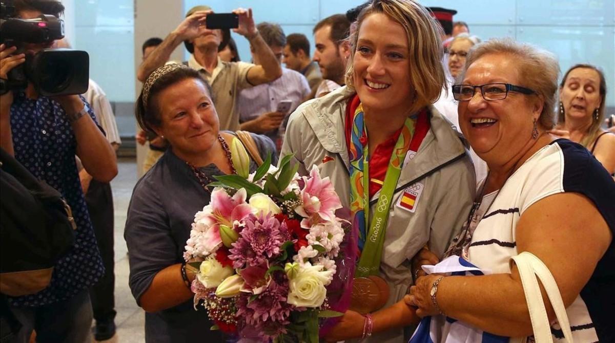 Mireia Belmonte, con sus dos medallas, posa junto a dos vecinas de Badalona, tras su llegada al aeropuerto de El Prat.