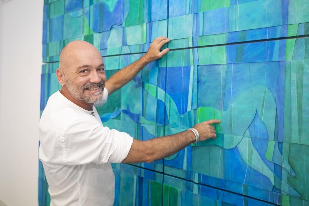 Juan Niubó, ante su obra favorita de la exposición, 'Flotando entre azules'.