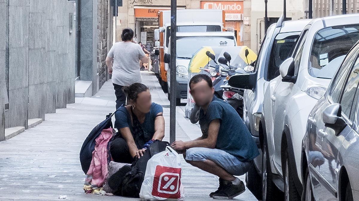 Dos tocxicómanos, después de drogarse en plena calle Egipciaques, en el Raval.