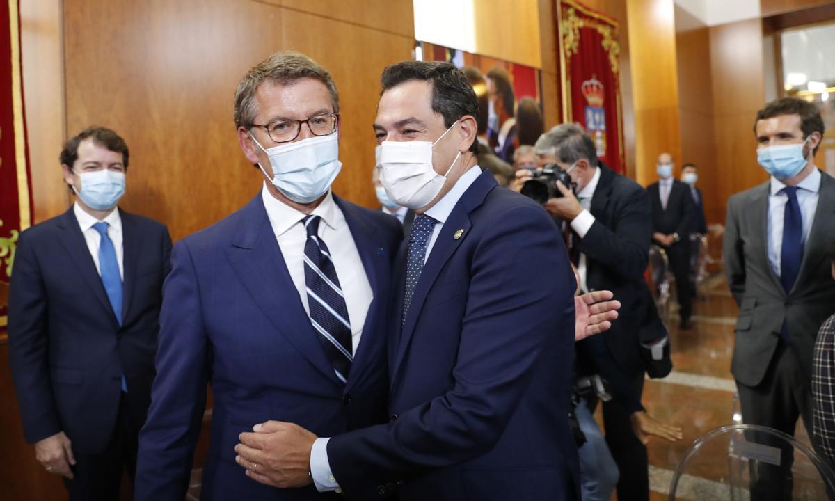 El presidente de Andalucía, Juan Manuel Moreno, felicita al líder de la Xunta, Alberto Núñez Feijóo, por su toma de posesión, el 5 de septiembre. En segundo plano, a la derecha, Pablo Casado.