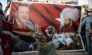Una mujer posa ante un cartel con la representación del presidente turco, Recep Tayyip Erdogan, y del sultán otomano Mehmet II, ayer en Estambul.
