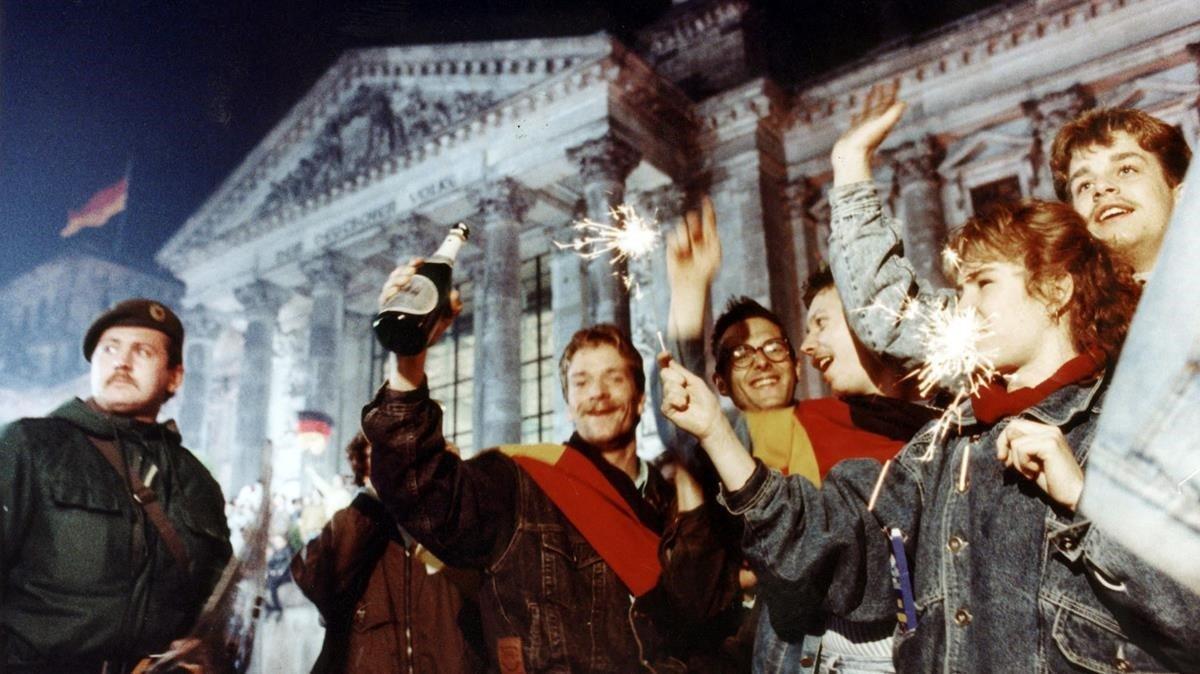 Unos jóvenes celebran la reunificación frente al edificio del Reichtag, el 3 de octubre de 1990.