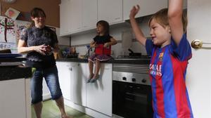 Pip Nolan junto a sus hijos Luca (con los brazos en alto)y Olive, en la cocina de su piso, en la plaza de Tetuan.